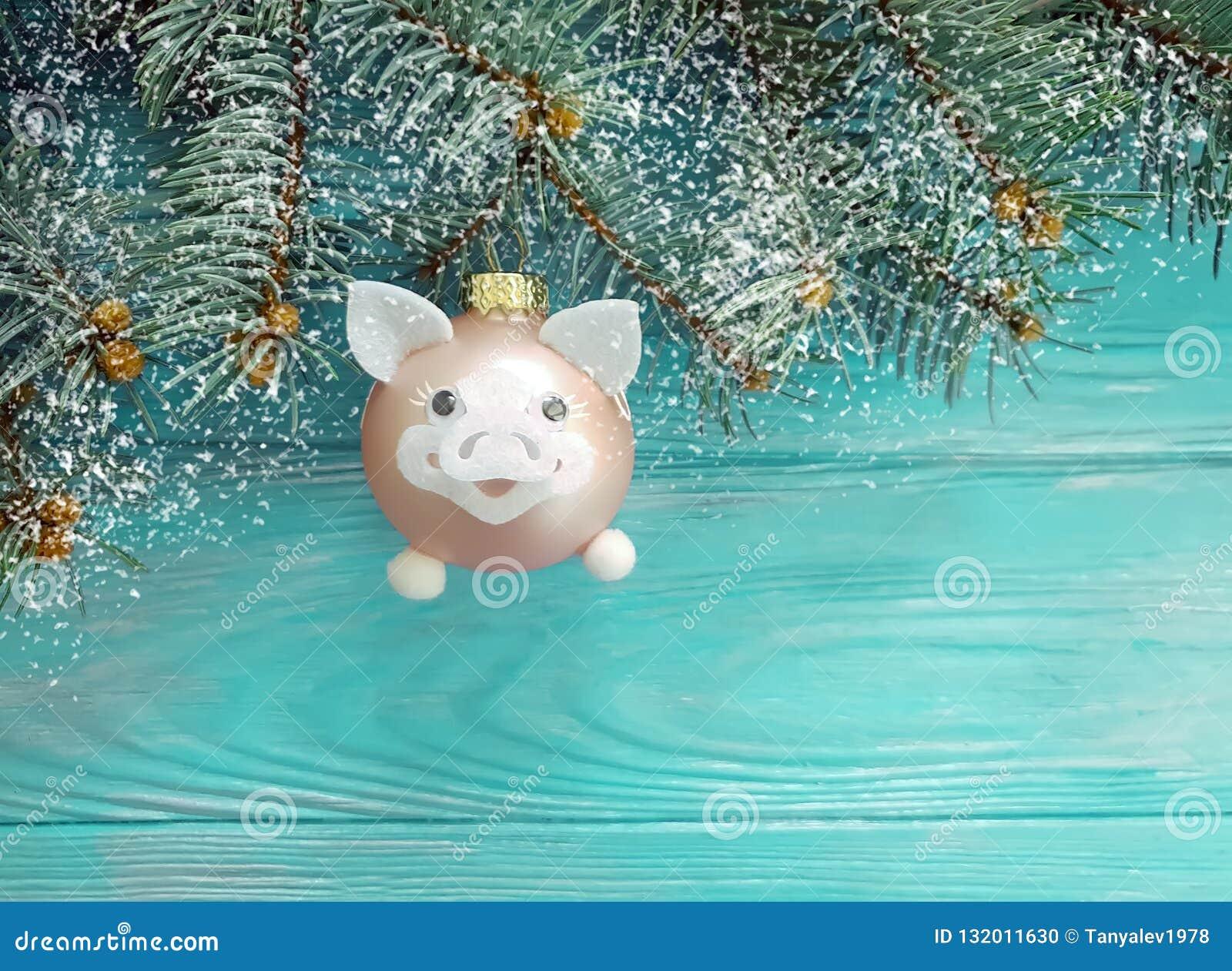 Kerstmisstuk speelgoed varkenskaart op een houten achtergrond, sneeuw, boomtak
