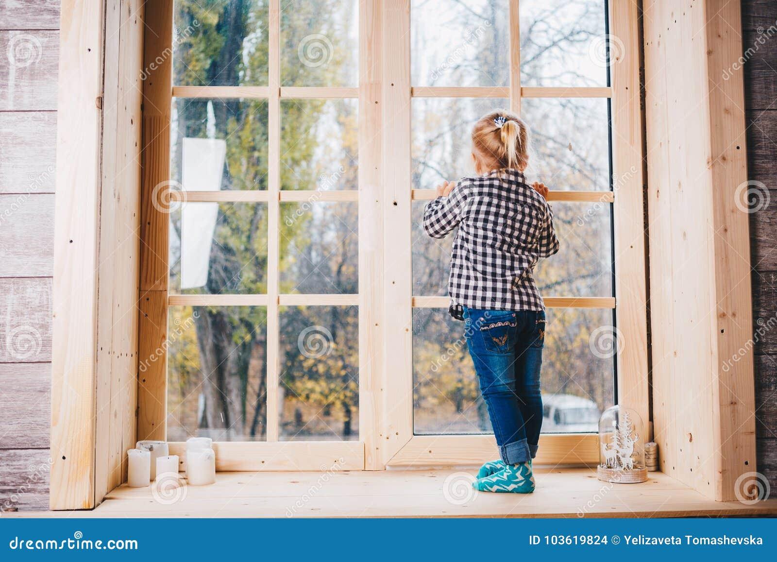 Kerstmistak en klokken Een kind met blondehaar in warm sokken, jeans en overhemd bevindt zich met haar die terug op windowstick,