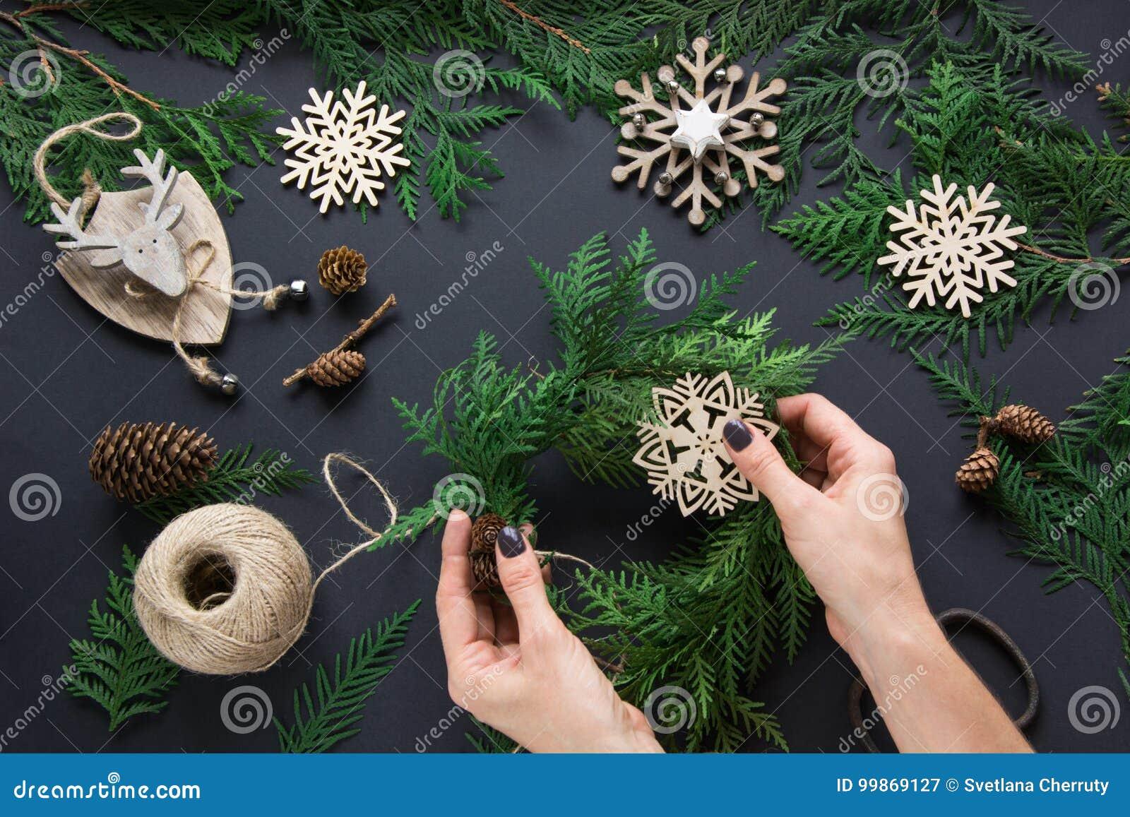 Kerstmisworkshop van kroon, decor, streng, takjes en sneeuwvlokken De vrouw bereidt een kroon voor Bovenkant v
