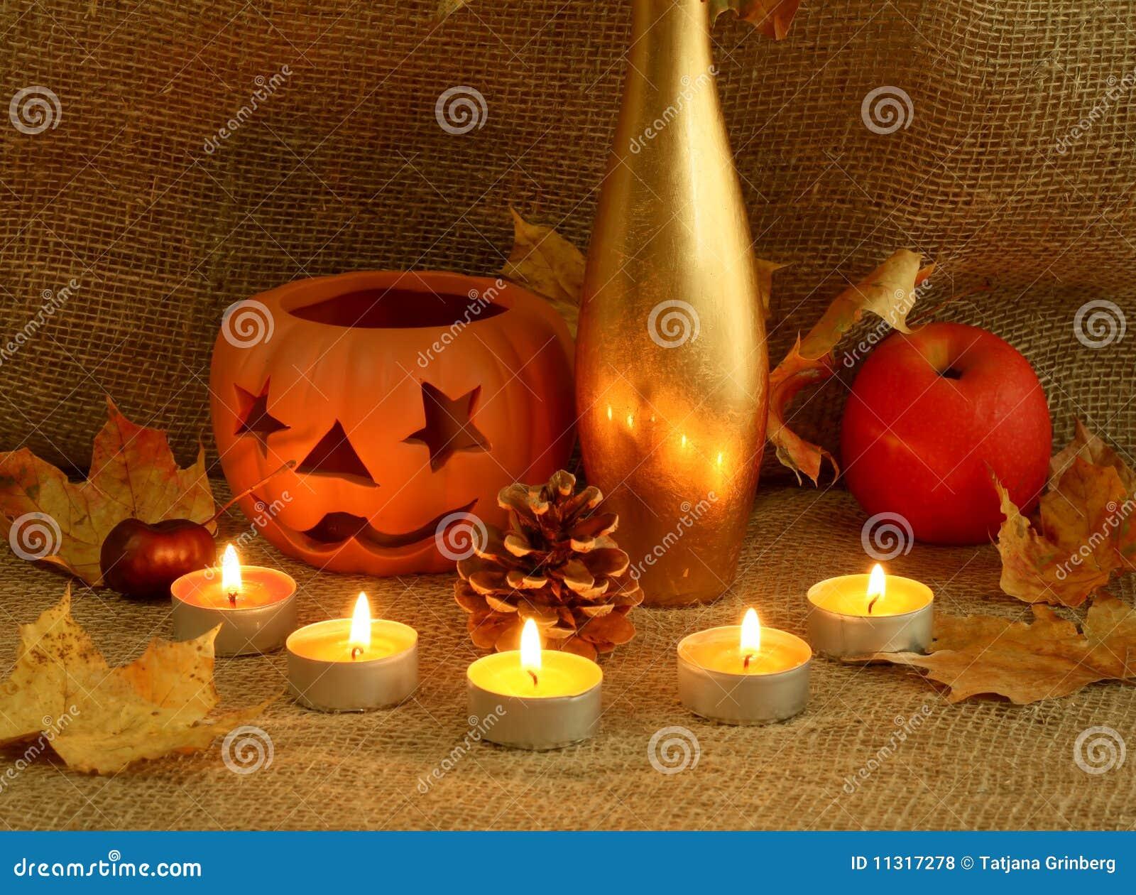Kerzen, Lehmkerzenhalter, trockene Blätter und Apfel.