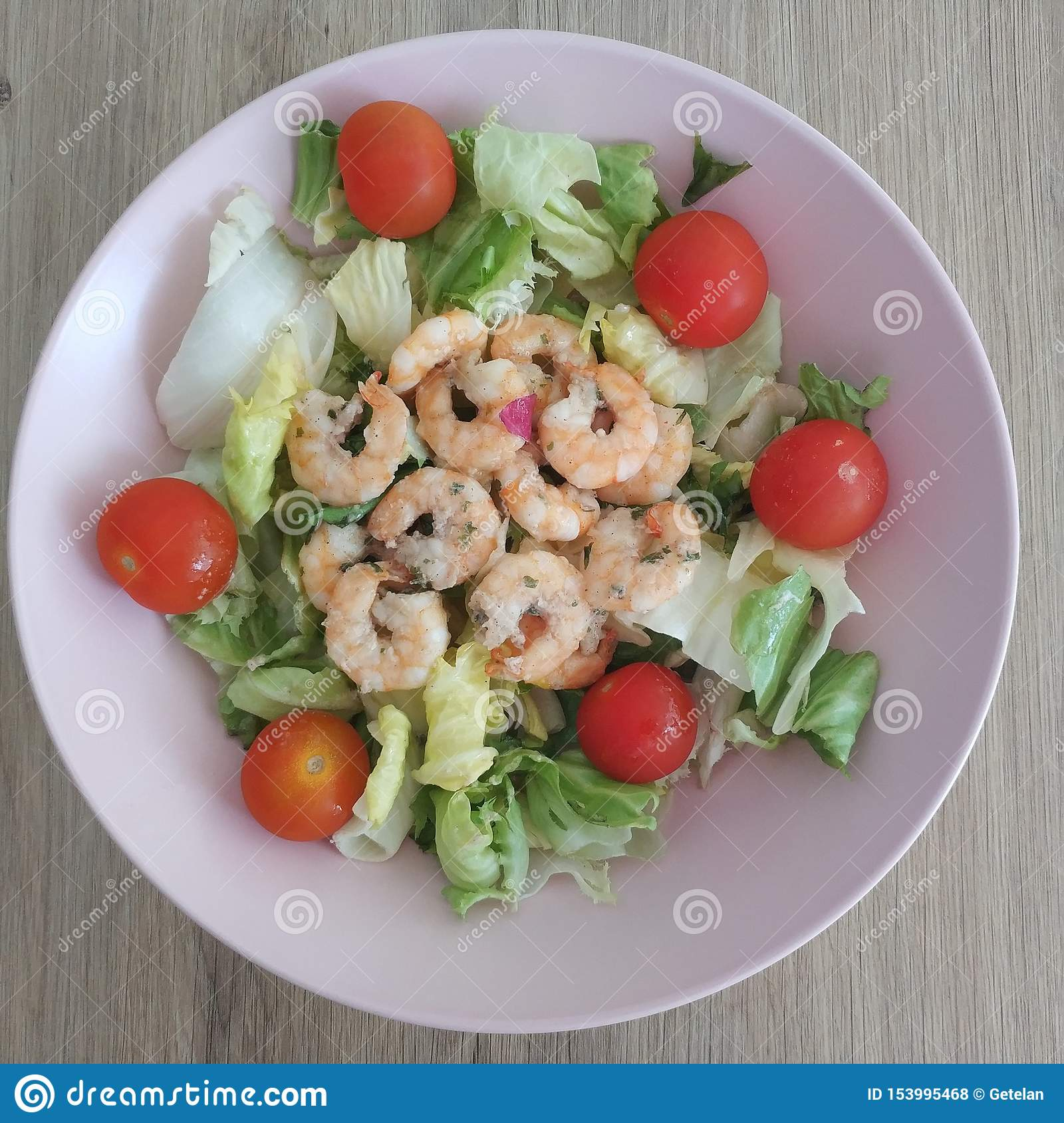 Ketogenic meal, shrimp salad with lettuce mix and tomatoes. Keto food for weight loss.