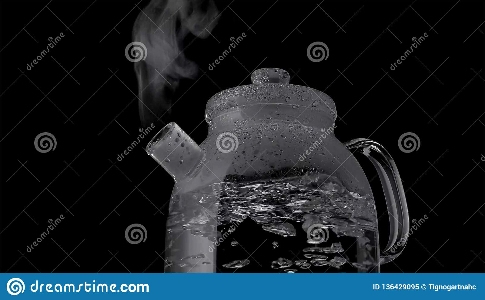 Kettle with boiling water and steam isolated on black background