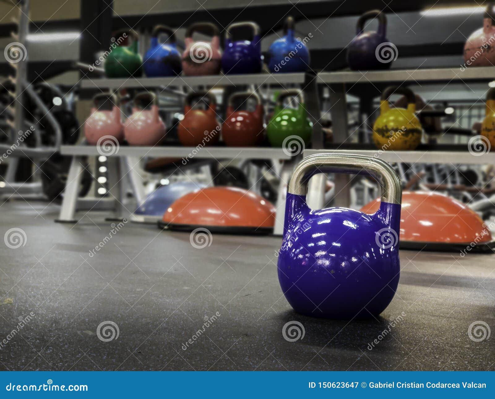 Kettlebell på en idrottshall med mer färgrik kettlebells på bakgrunden