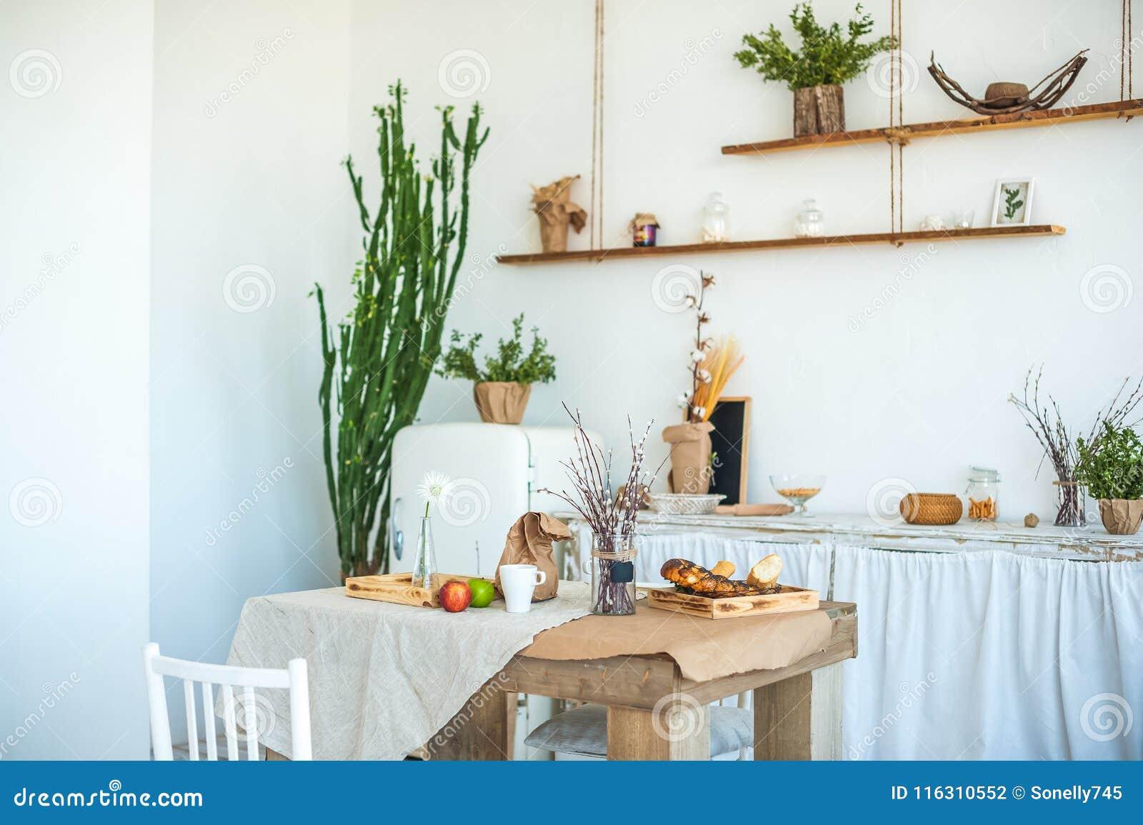 Keuken in rustieke stijl in de zomer De lente lichte geweven keuken met een oude koelkast, houten lijst Een houten dienblad met e