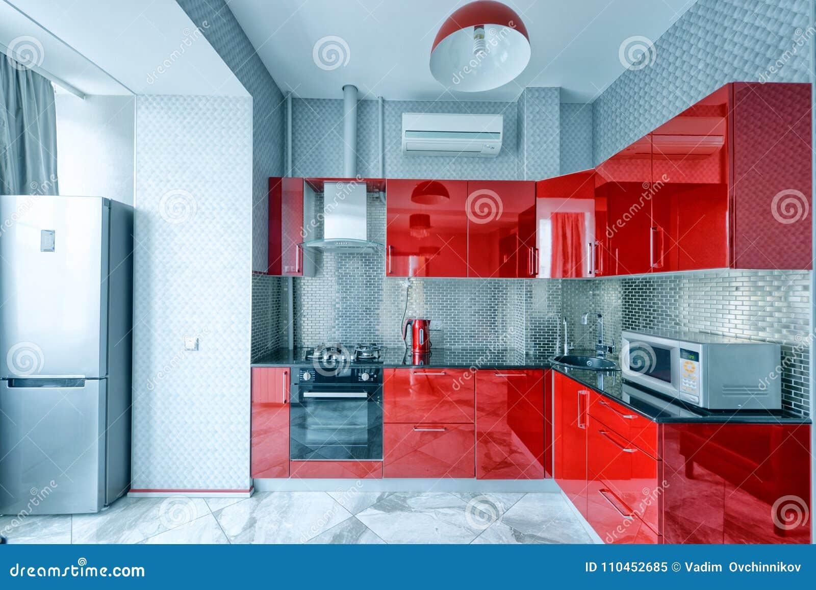 Keukenbinnenland in rode kleuren modern huis stock afbeelding