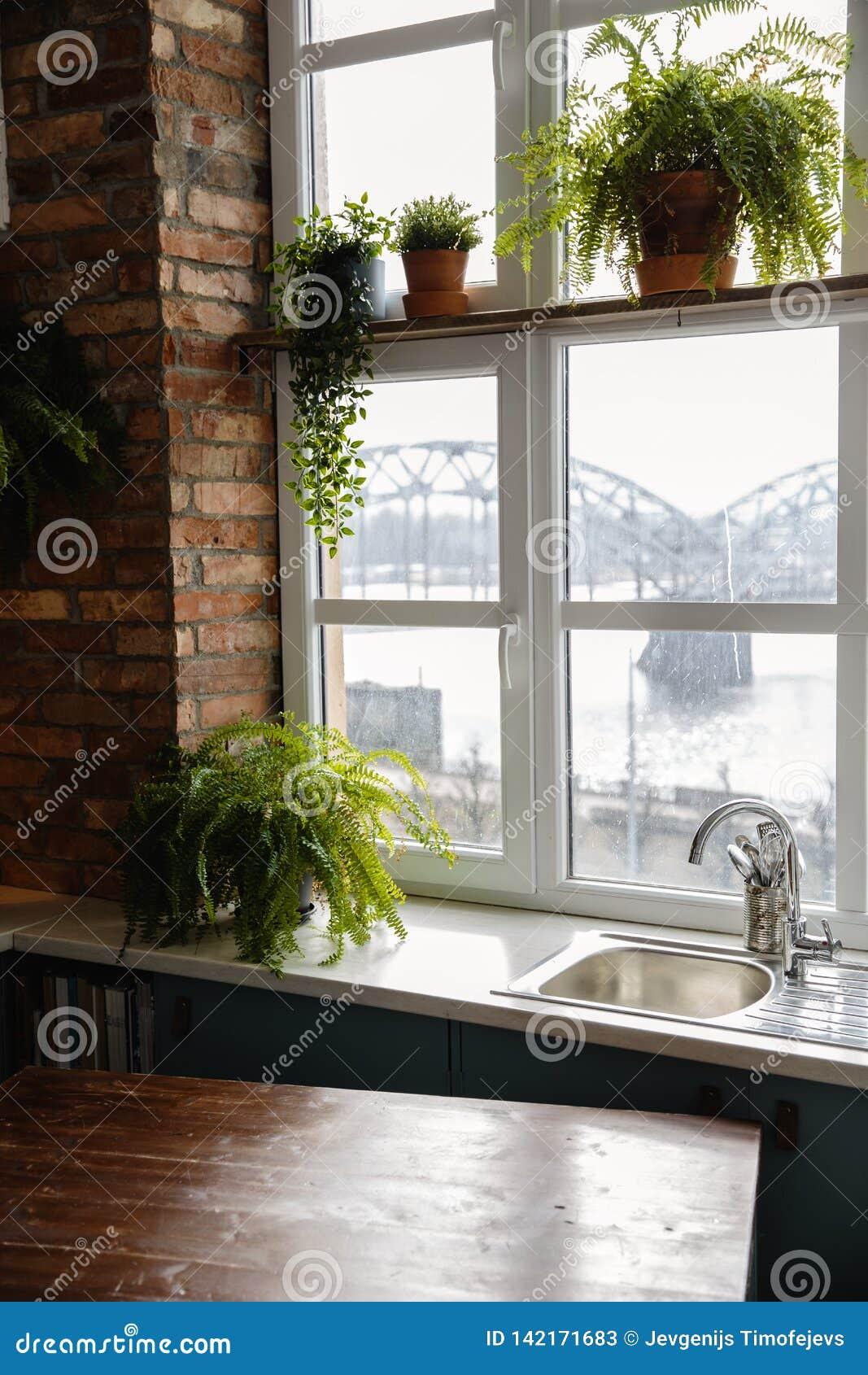 Keukenzolder met ontworpen bakstenen muur en een venster dat de Spoorwegbrug in Riga, Letland onder ogen ziet