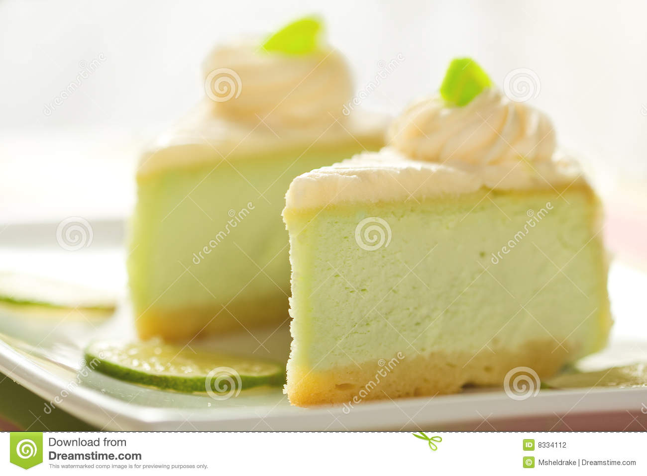 Two slices of key lime cheesecake on a large white platter.