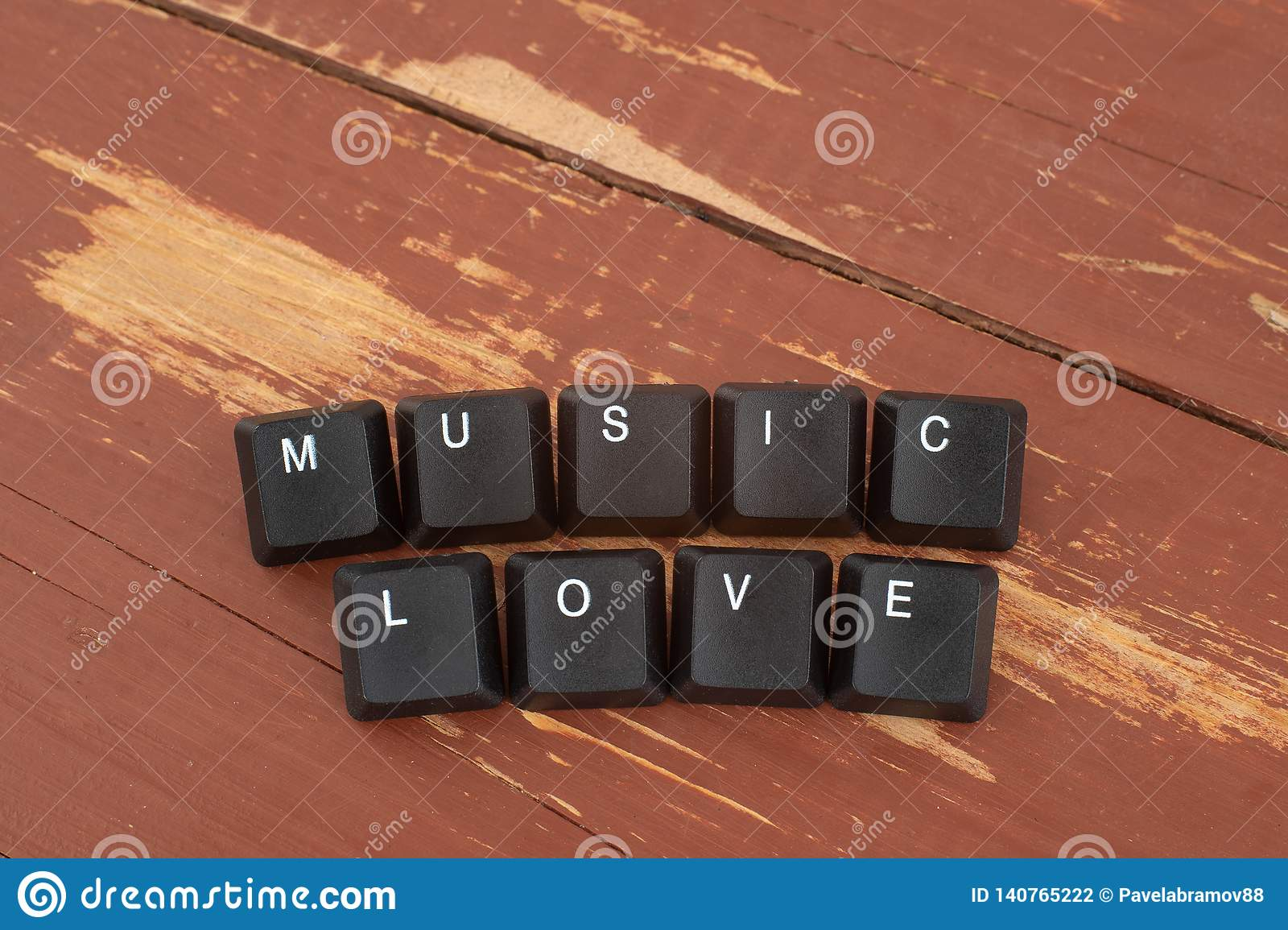 The keyboard buttons the inscription love music. Wooden background