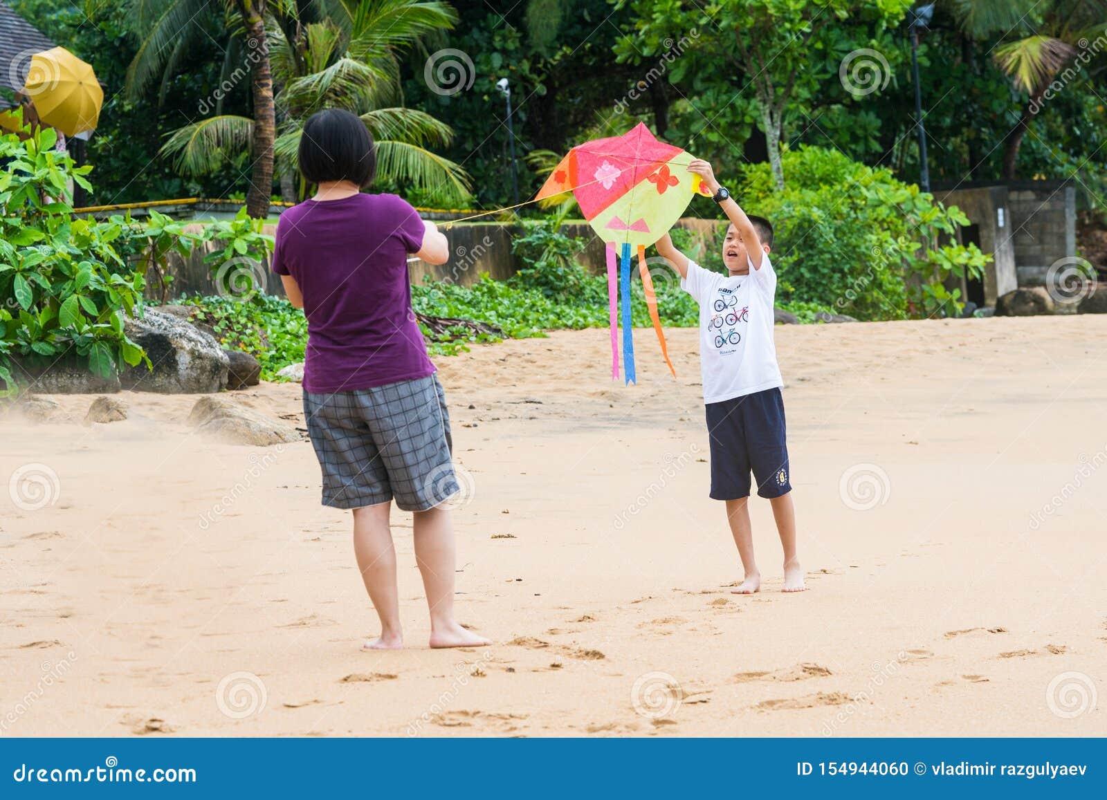 Khaoak, Tailandia, il 20 luglio 2019: Il ragazzo asiatico e la sua mamma stanno pilotando un aquilone sulla spiaggia