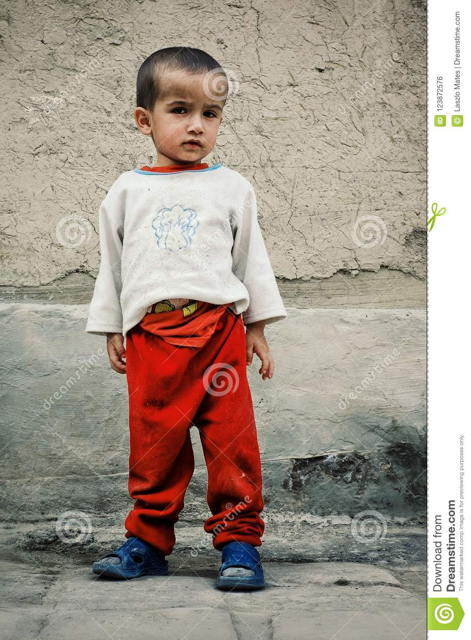 Young boy waiting for his father in the historical walled city of the silk road