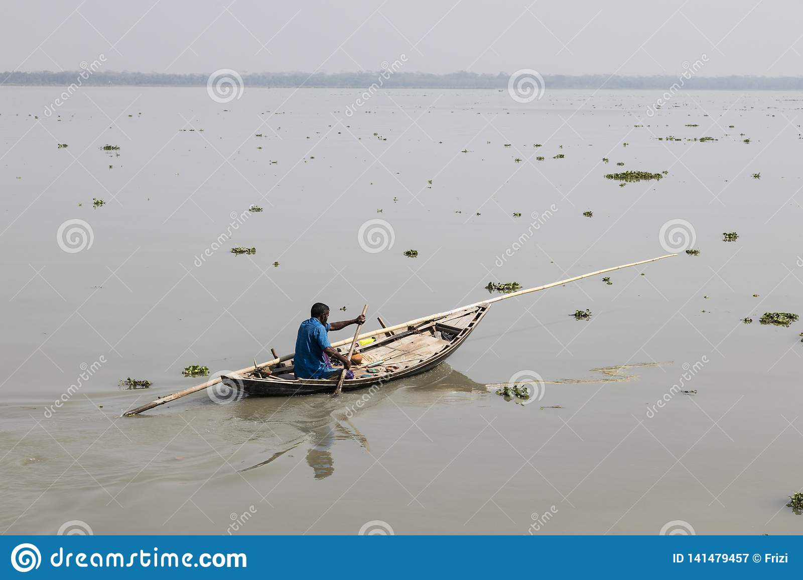 Khulna, Bangladesh, el 1 de marzo de 2017: Hombre que rema con un pequeño barco de madera en un río cerca de Khulna