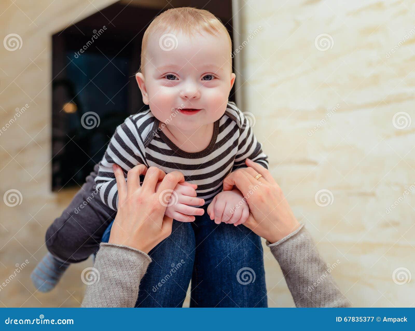 Kicherndes Baby oben auf Knien des Erwachsenen
