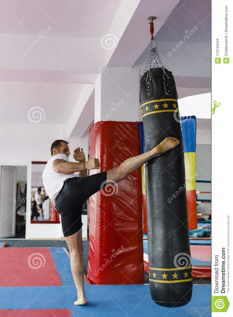 Kickbox fighter training in a gym with punch bags, see the whole