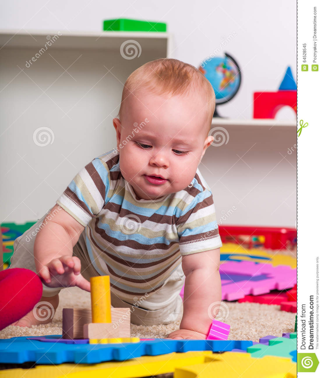 Baby Floor Toys : Kid baby boy plying with puzzle toy on floor stock photo