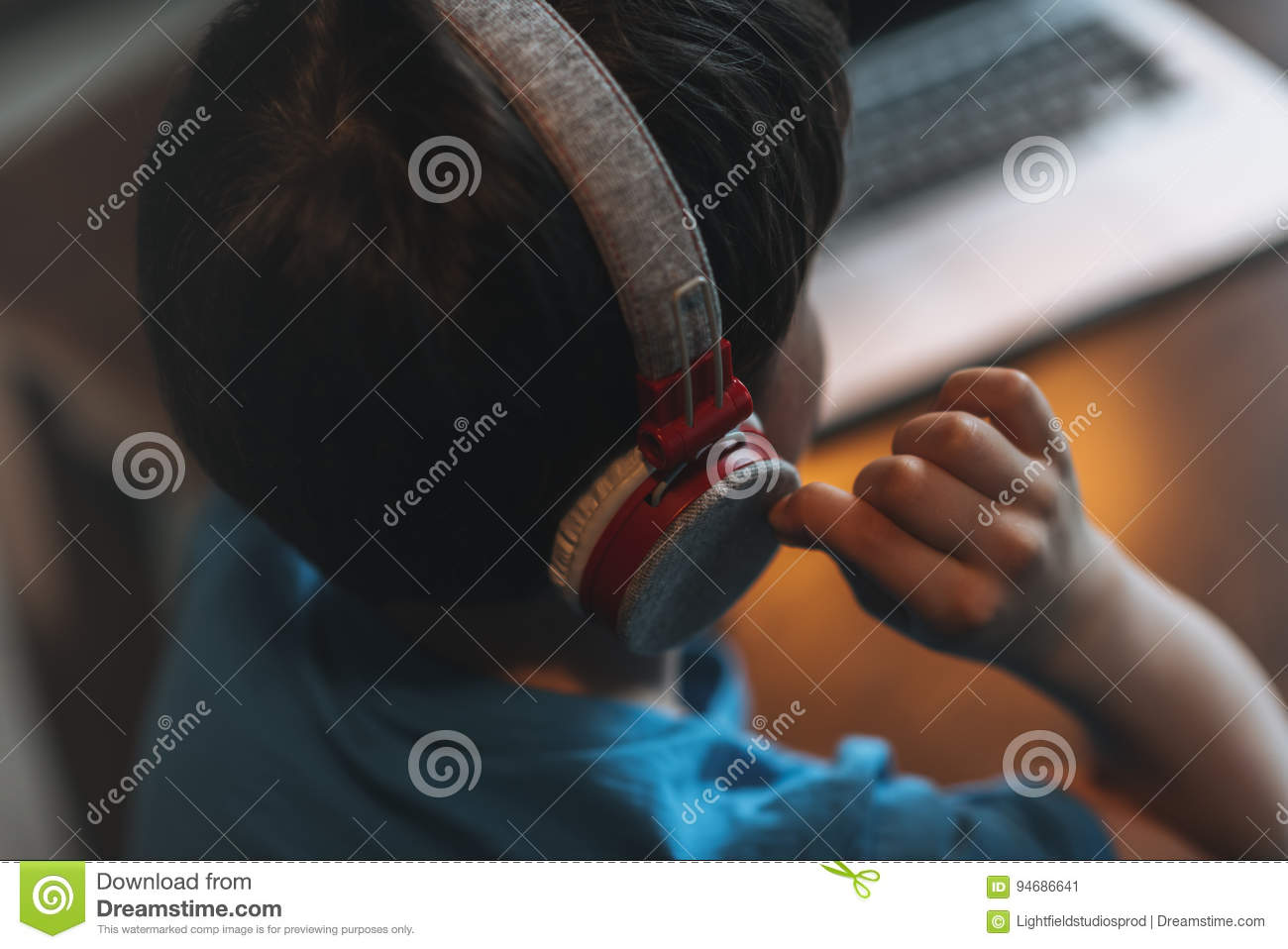 Download kid boy listening music in headphones while sitting stock image image of indoors