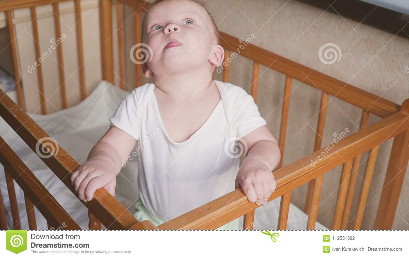 Kid In The Crib Looks Around Speaks Jumps And Smiles Stock Footage
