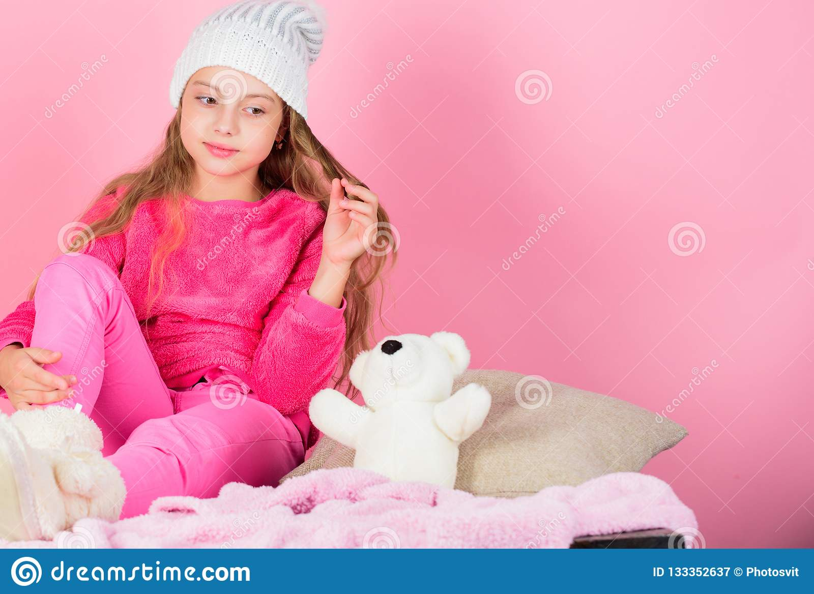 Kid cute girl play with soft toy teddy bear pink background. Unique attachments to stuffed animals. Child small girl
