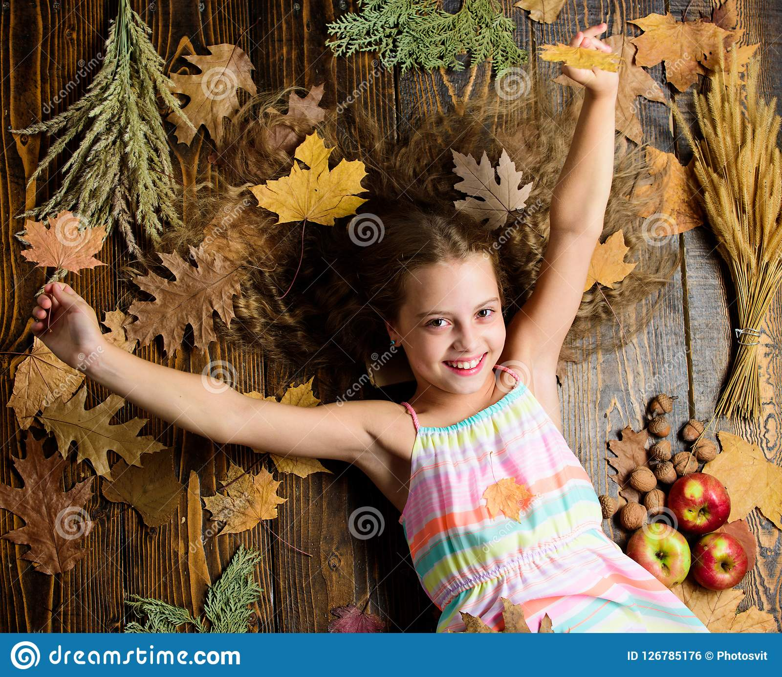 Kid cute girl relax wooden background autumn attributes top view child long hair with dry