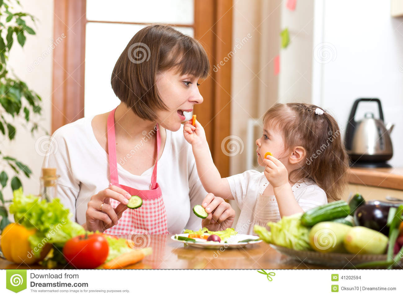 Kid Daughter Feeding Mother Vegetables In Kitchen Stock Photo Image 41202594