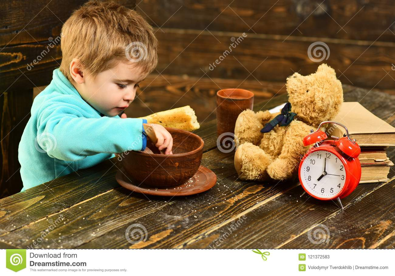 Kid eat food at wooden table. Kid enjoy meal with toy friend. Kid menu. Little kid eating. You are what you eat