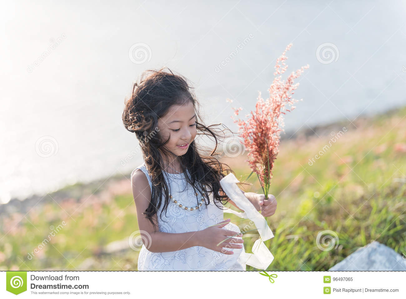 Kid fashion. Cute little asian girl wearing white clothes and flower grass in her hand.