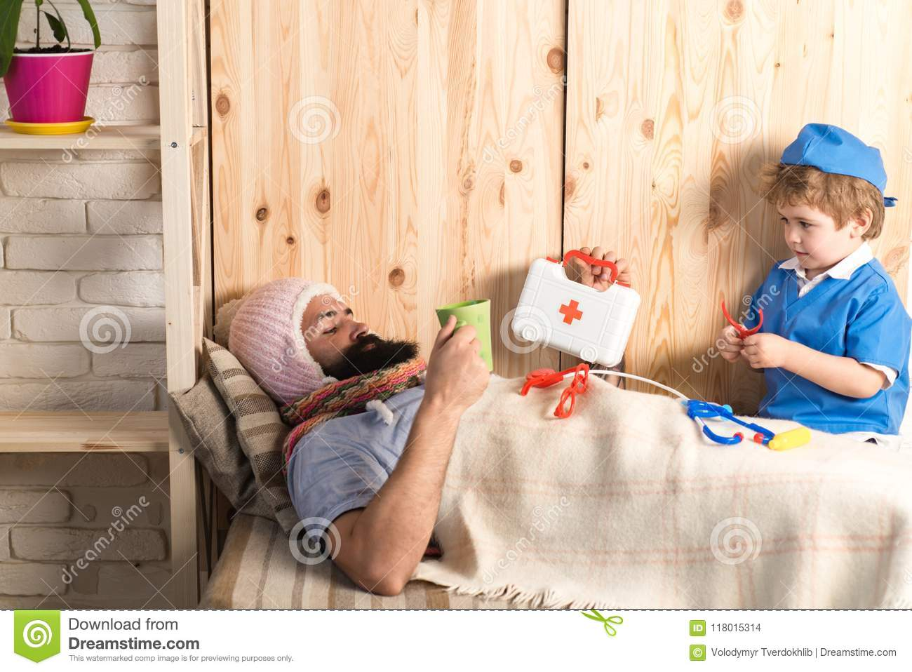 Kid and father playing hospital. Patient with flu lying in bed under woolen blanket. Doctor visiting sick bearded man at