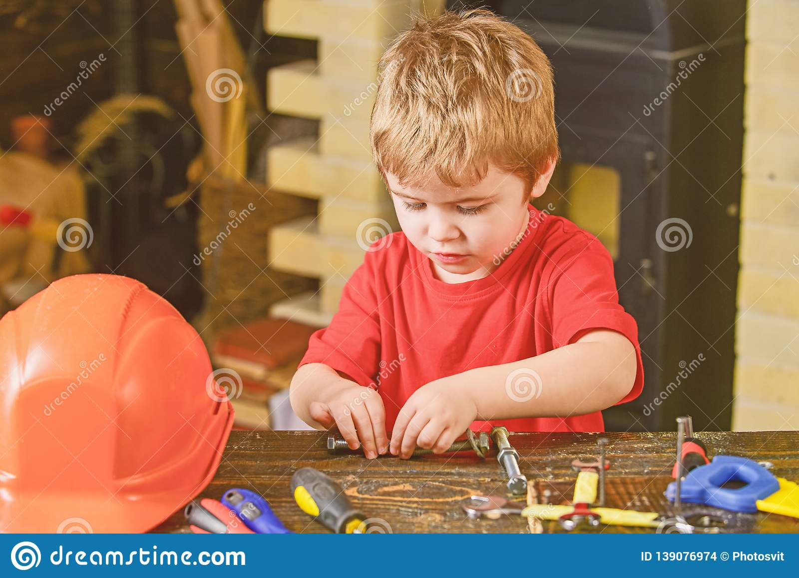 Kid fixing two metal details. Concentrated boy working with bolts. Preschooler helping in workshop
