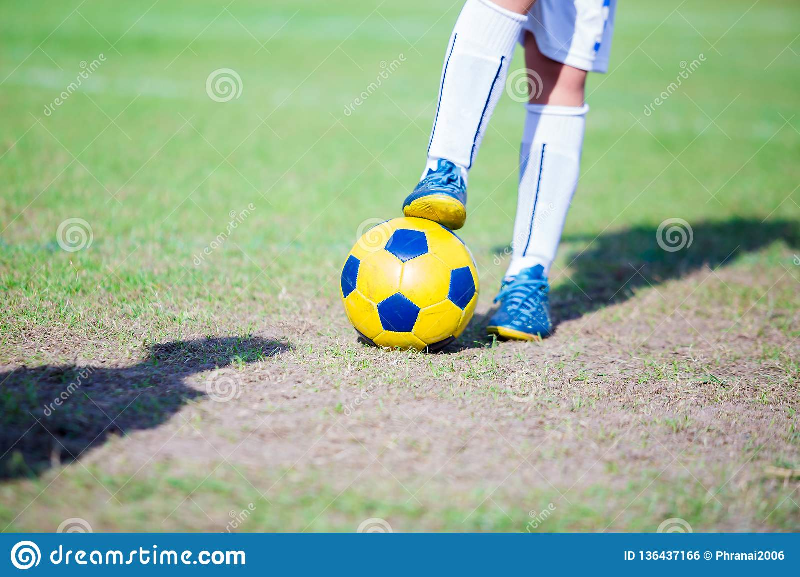 Kid football player standing and stepping on the ball