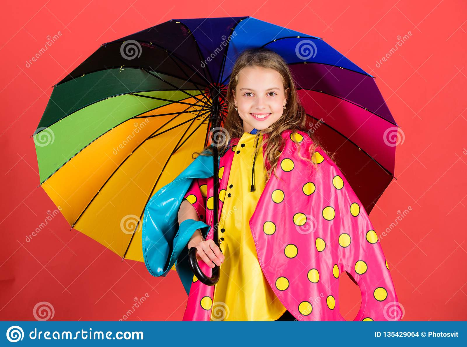 Kid girl happy hold colorful umbrella wear waterproof cloak. Enjoy rainy weather with proper garments. Waterproof