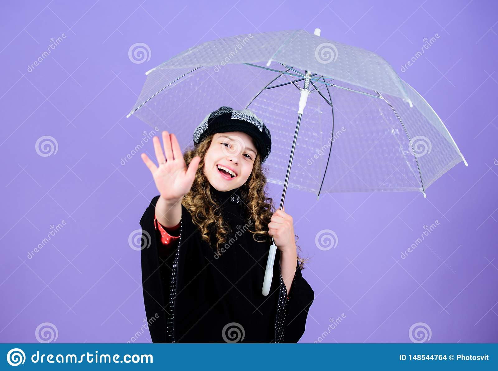 Kid girl happy hold transparent umbrella. Enjoy rainy weather with proper garments. Waterproof accessories make rainy