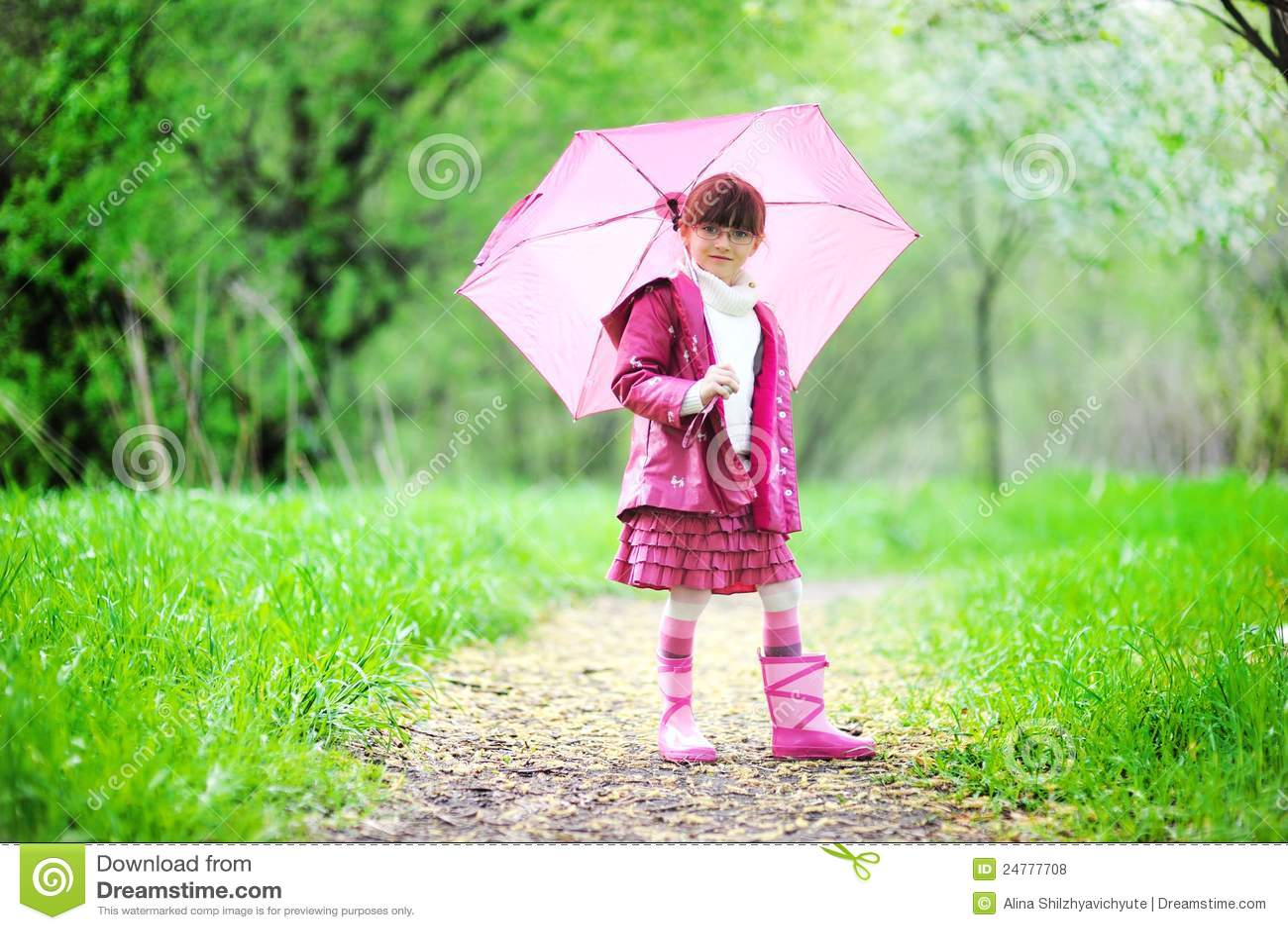 Kid girl posing outdoors with pink umbrella