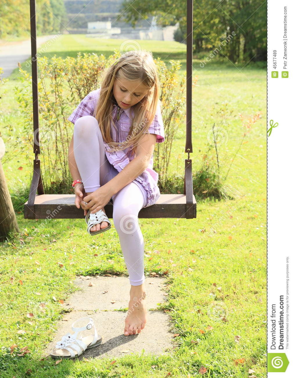 Kid - girl putting on shoes on swing