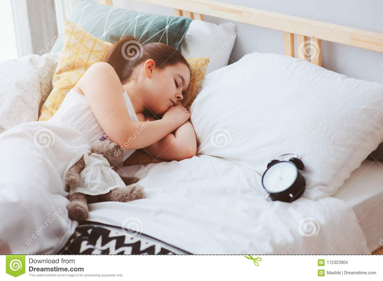 Kid girl sleeping in early morning in bed with alarm clock