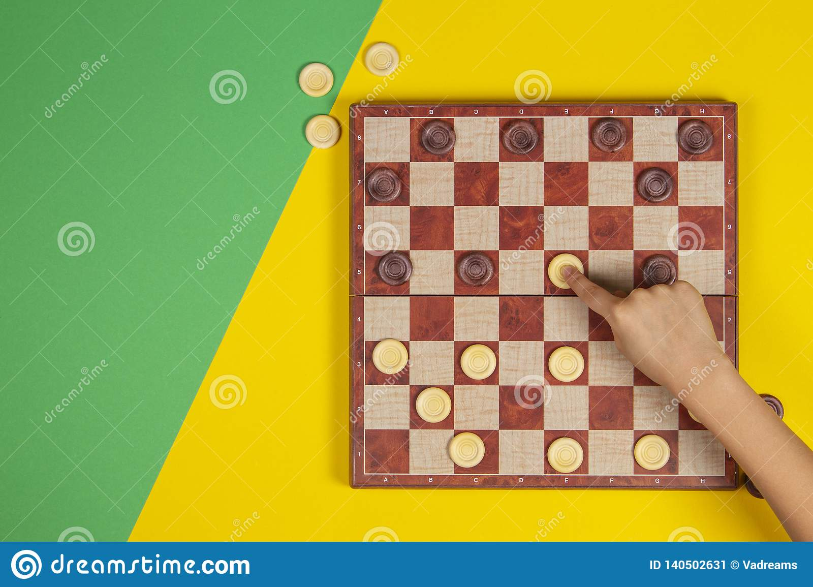 Child hand playing checkers on checker board game over yellow and green background, top view
