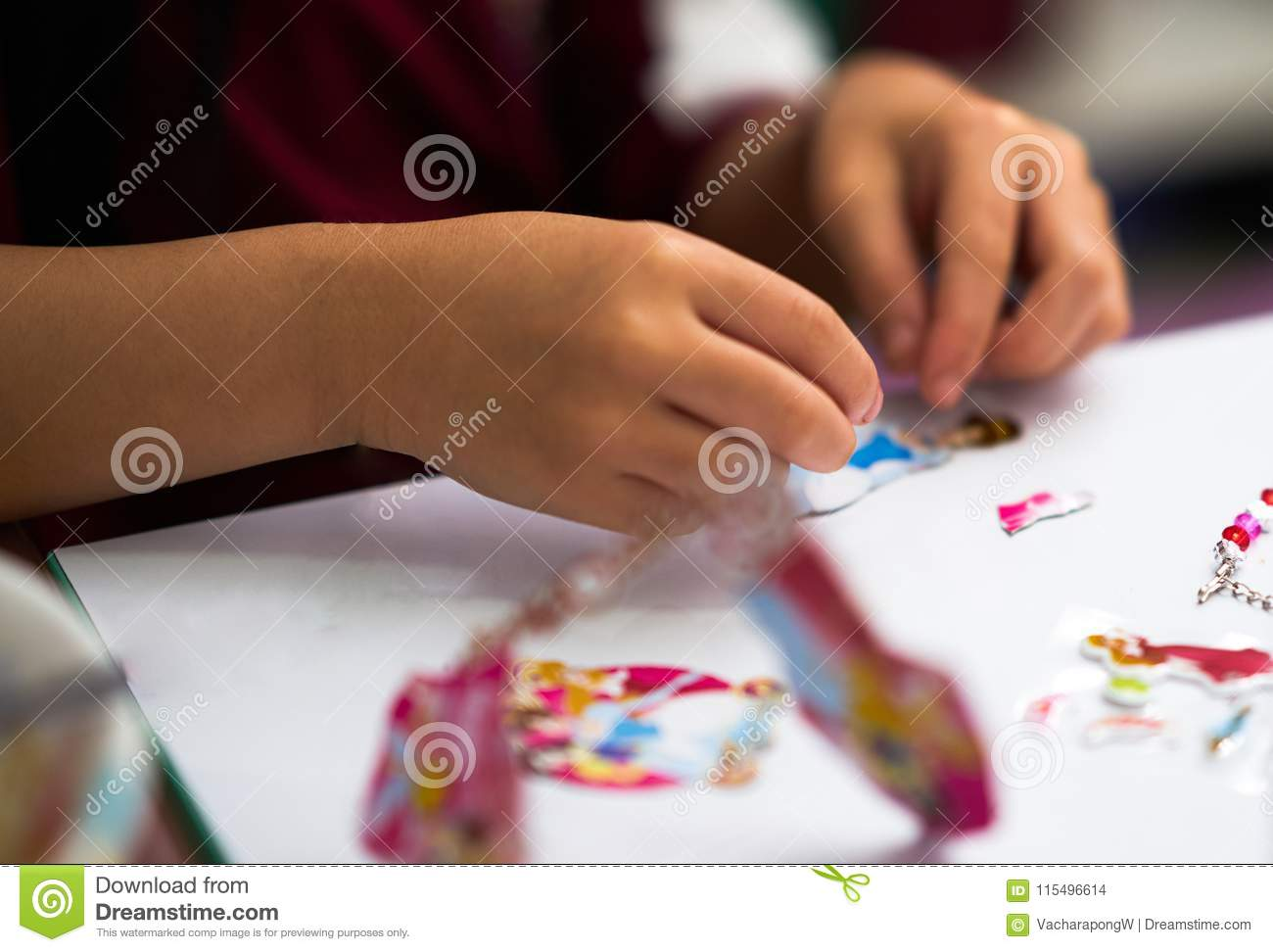 Kid hands view ,playing sticker of cartoon toy