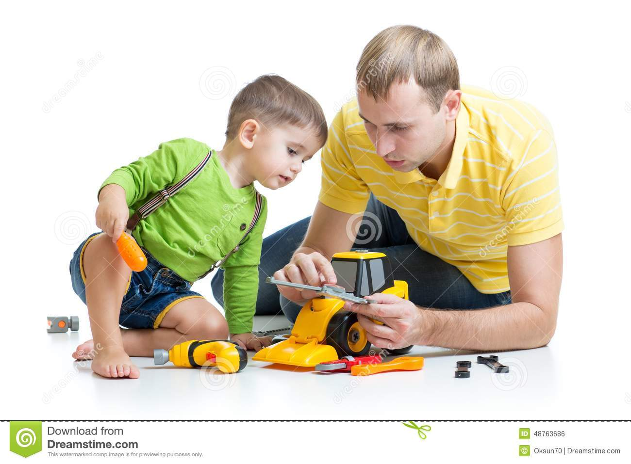 Boy Toys For Dads : Kid and his dad repair toy tractor stock photo image