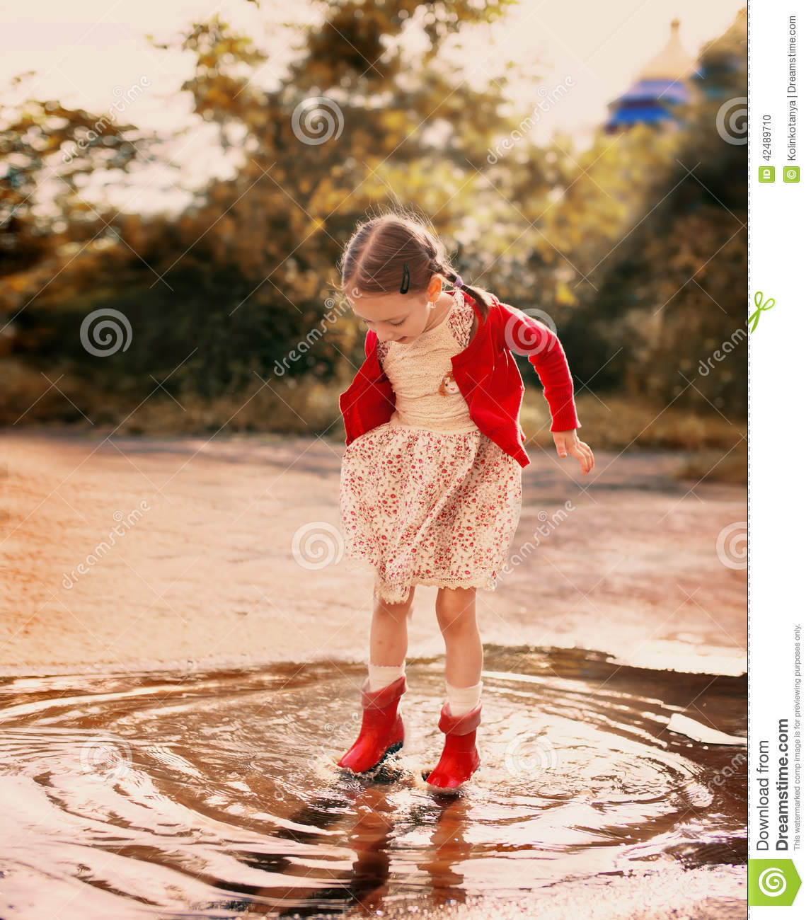 Cute little girl wearing red rain boots jumping into a puddle.