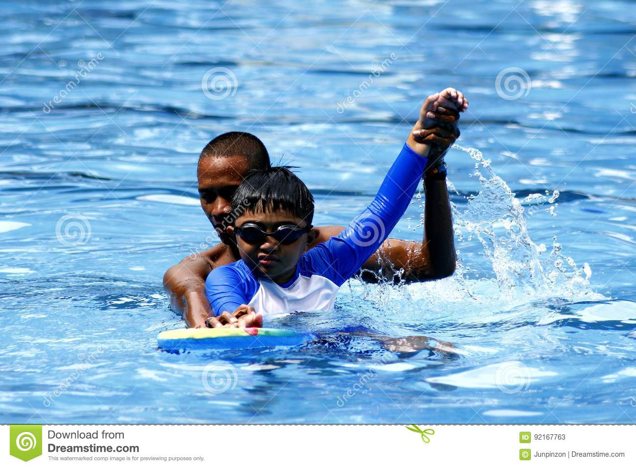 A kid learns how to swim with the help of a swimming coach.