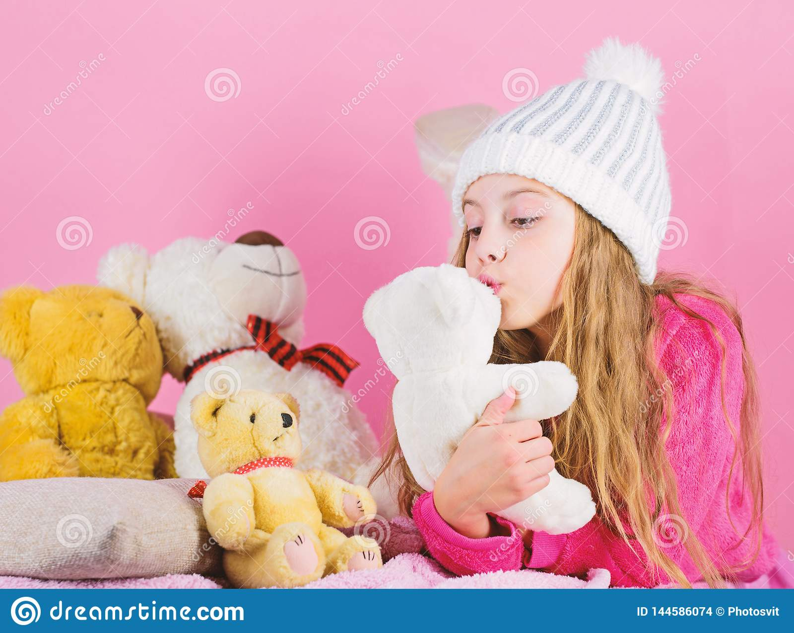 Kid little girl play with soft toy teddy bear on pink background. Teddy bears help children handle emotions and limit