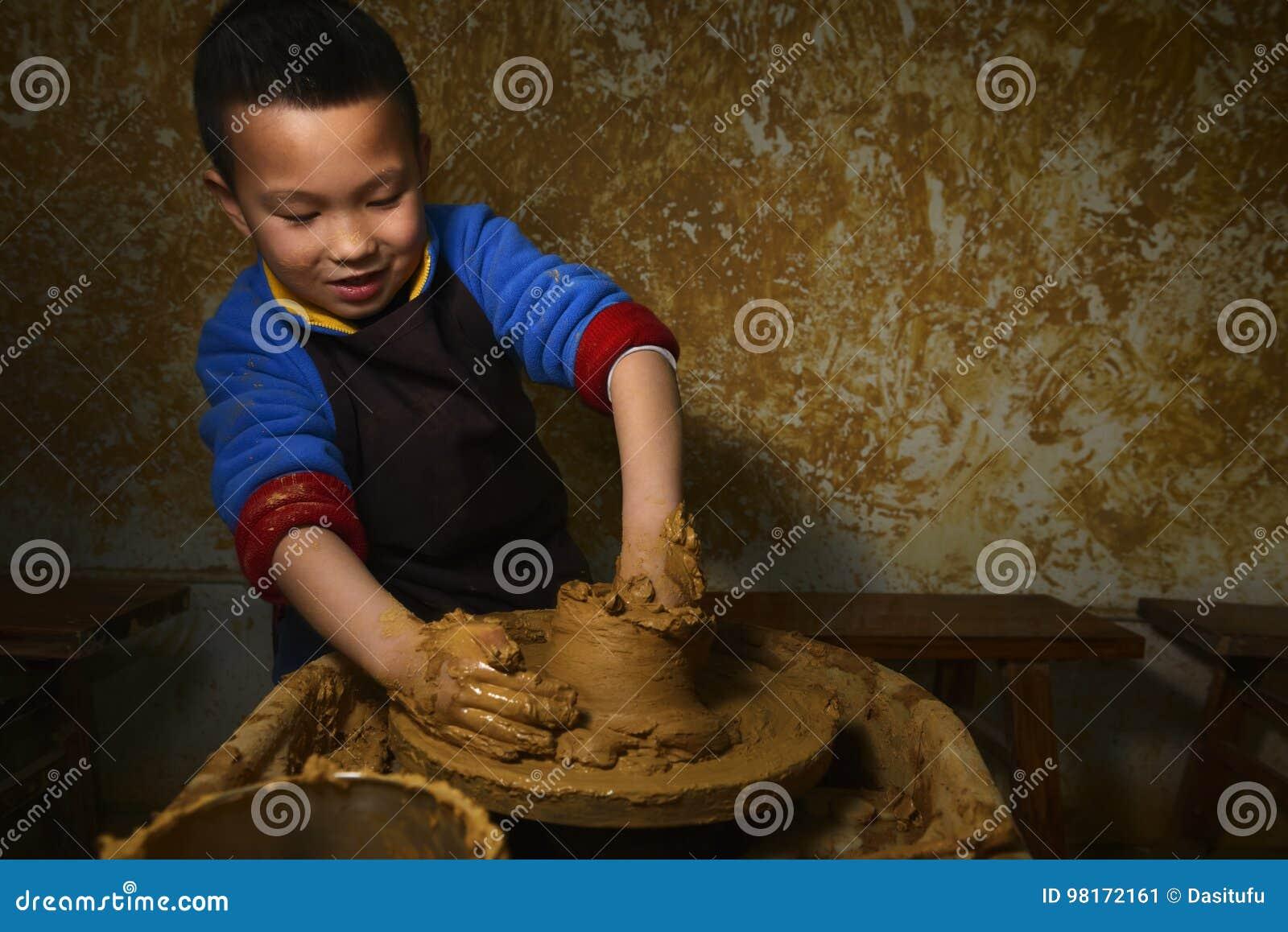 Kid making pottery