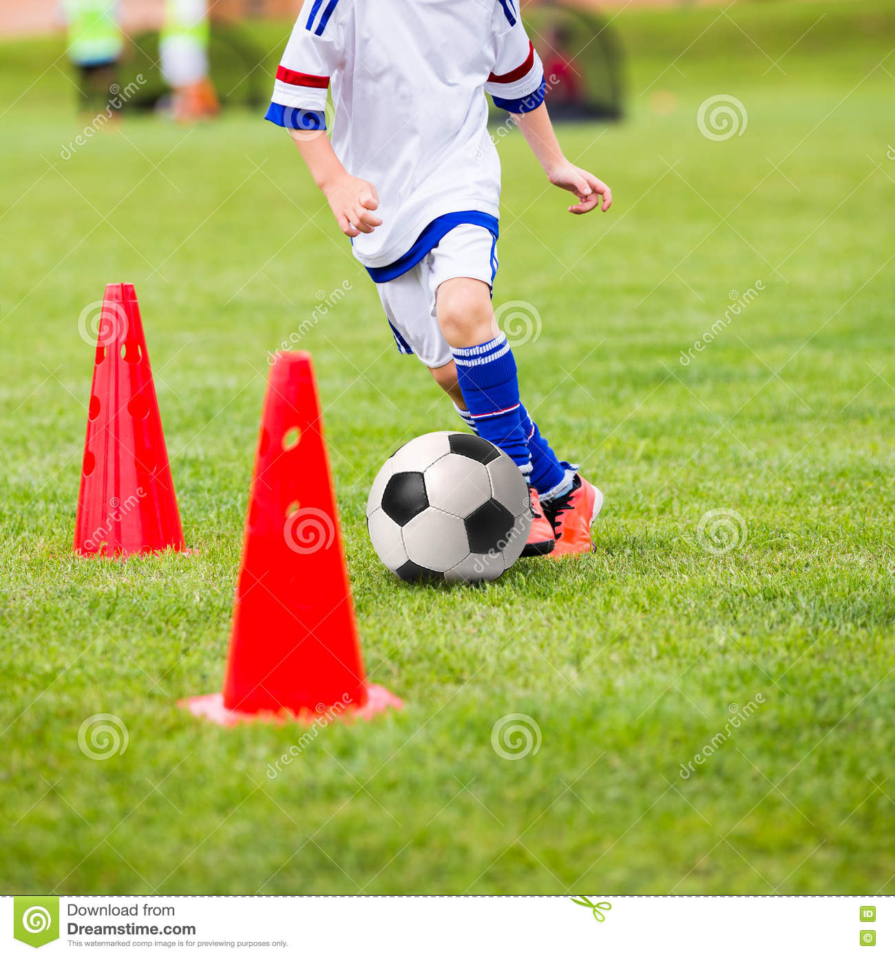 Kid playing soccer. Training football session for children. Boys is training with soccer ball and bollards on the field