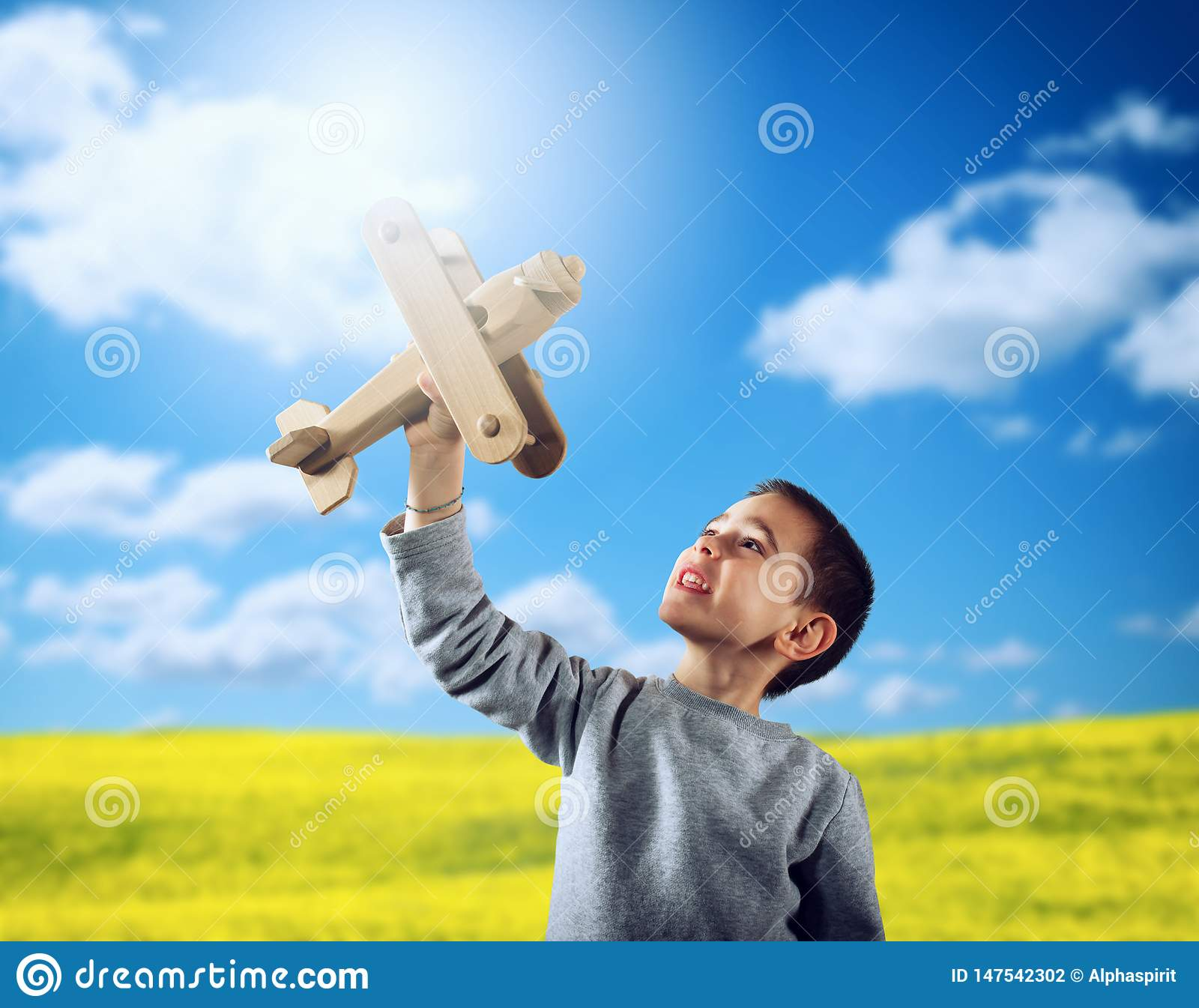 Kid plays with a wooden toy airplane