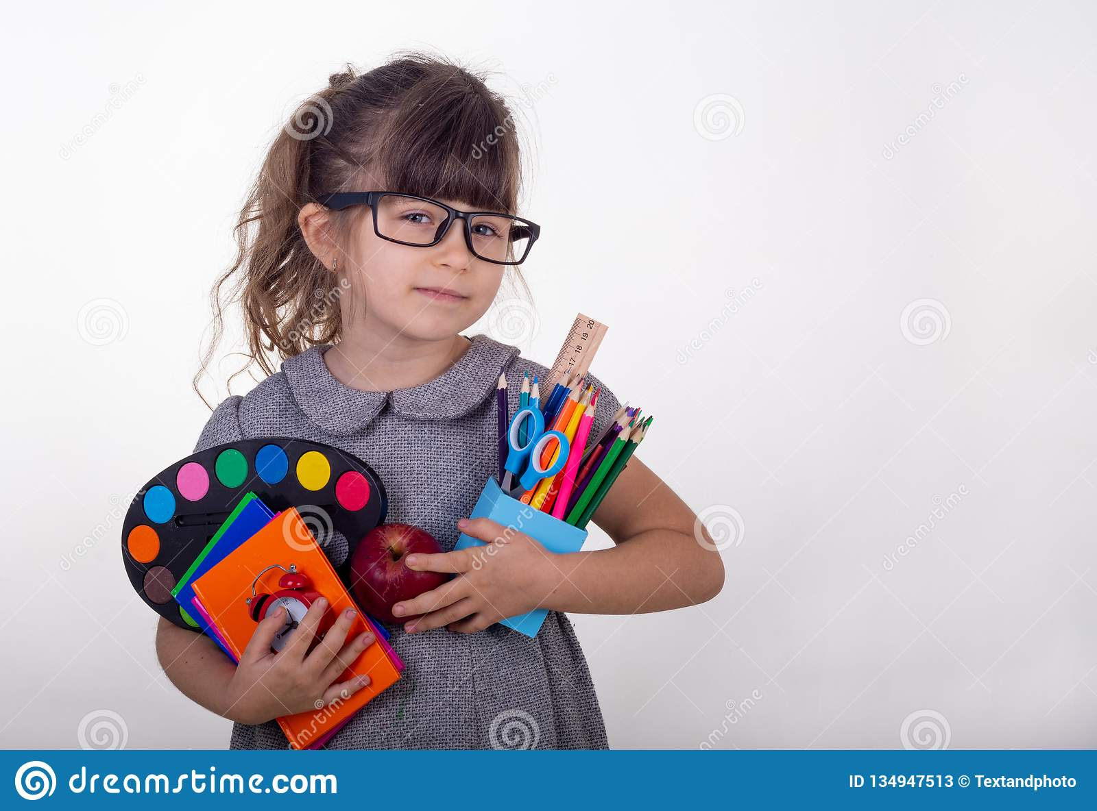 Kid ready for school. Cute clever child in eyeglasses holding school supplies: pens, notebooks, scissors and apple.