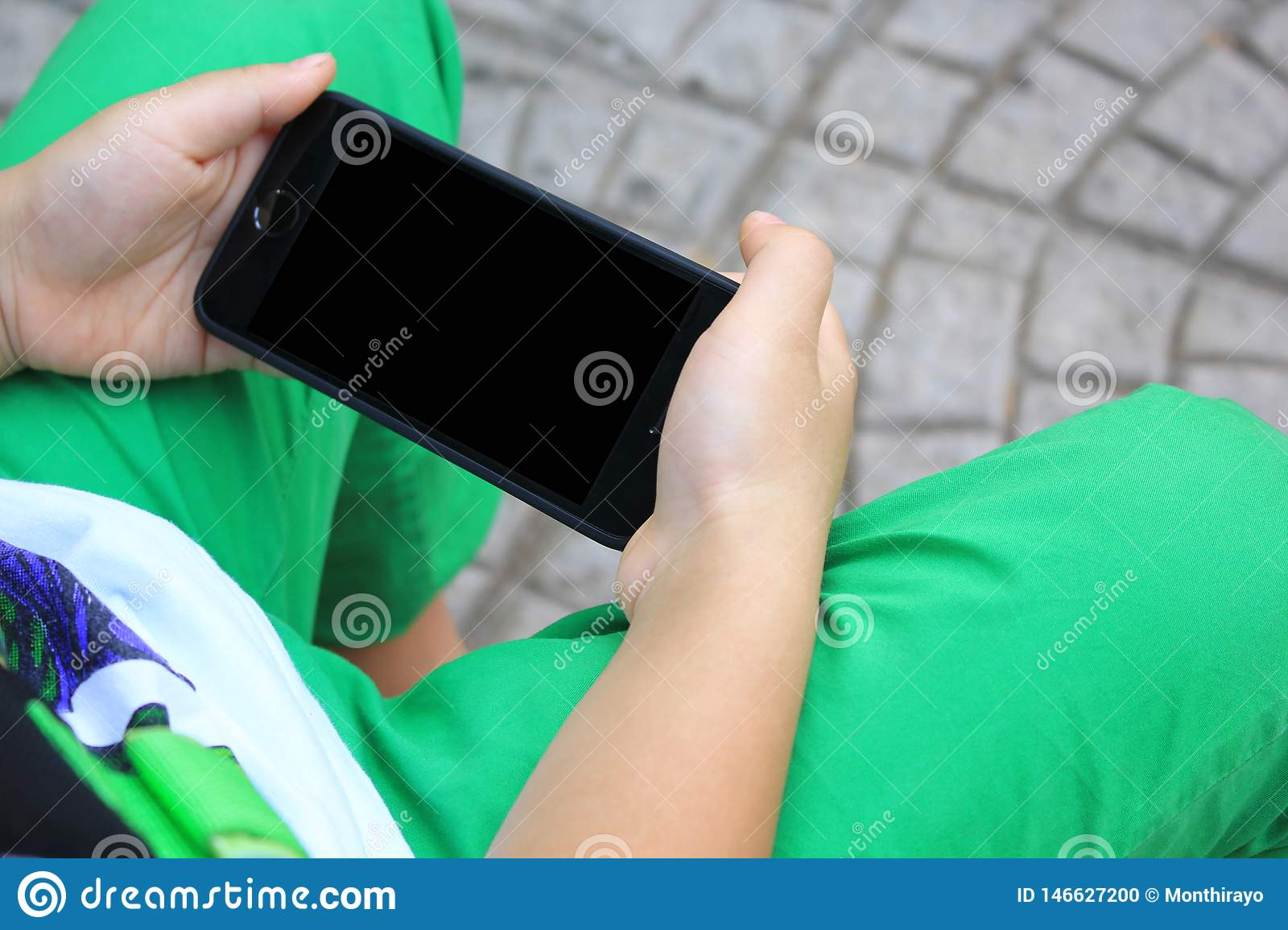 Kid`s hands hold smart phone for playing and education