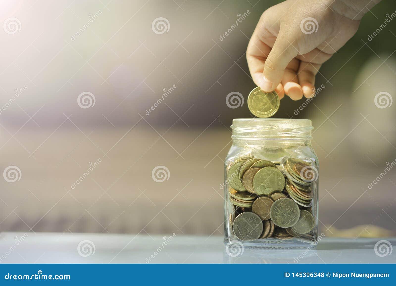 Kid saving coin in glass piggy bank