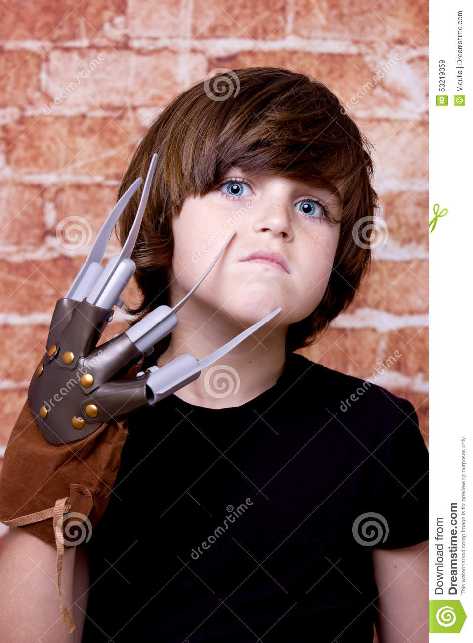 Kid with scary nails on face. Brick wall