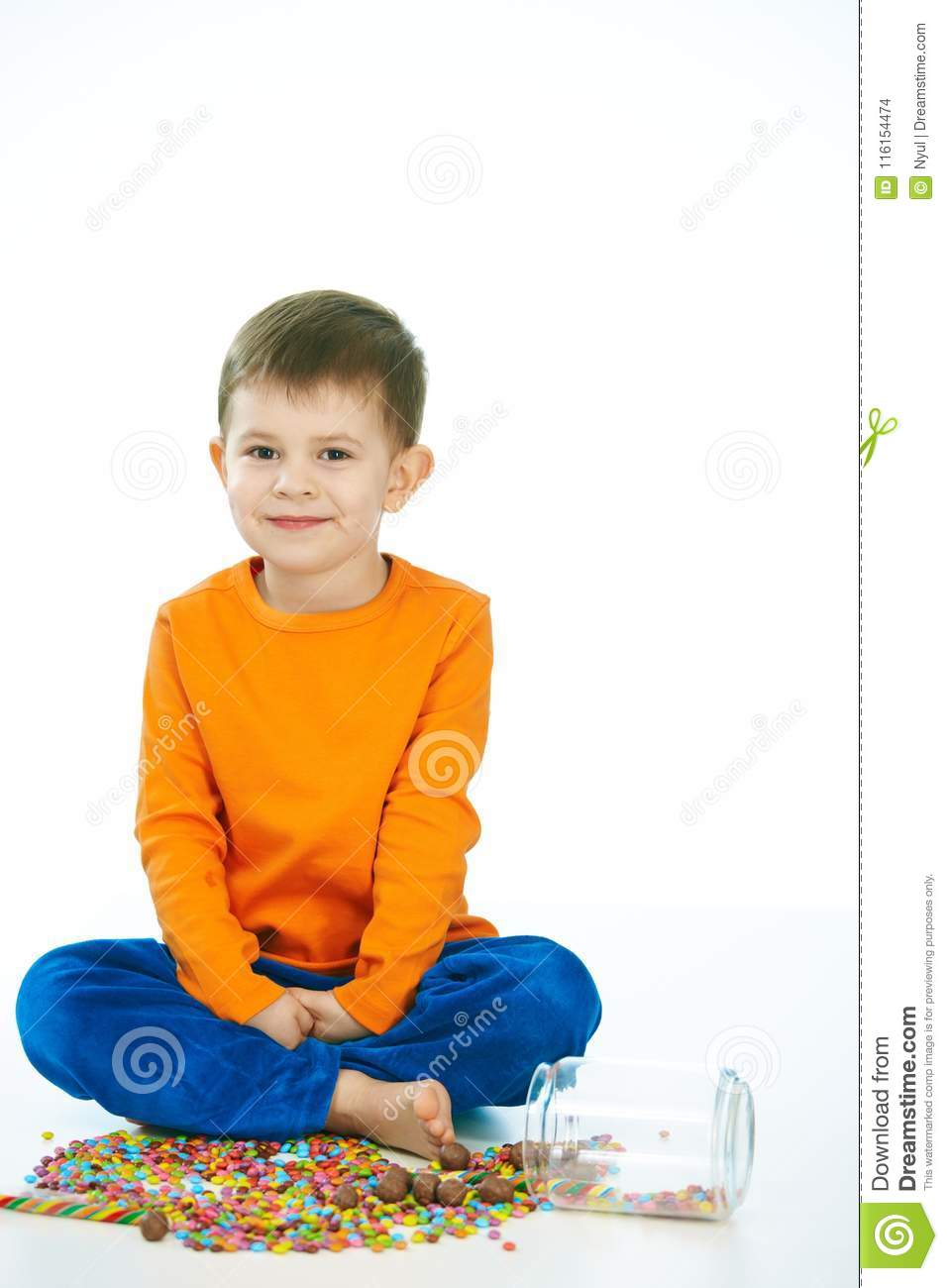 Kid sitting cross-legged with sweet jar spilled