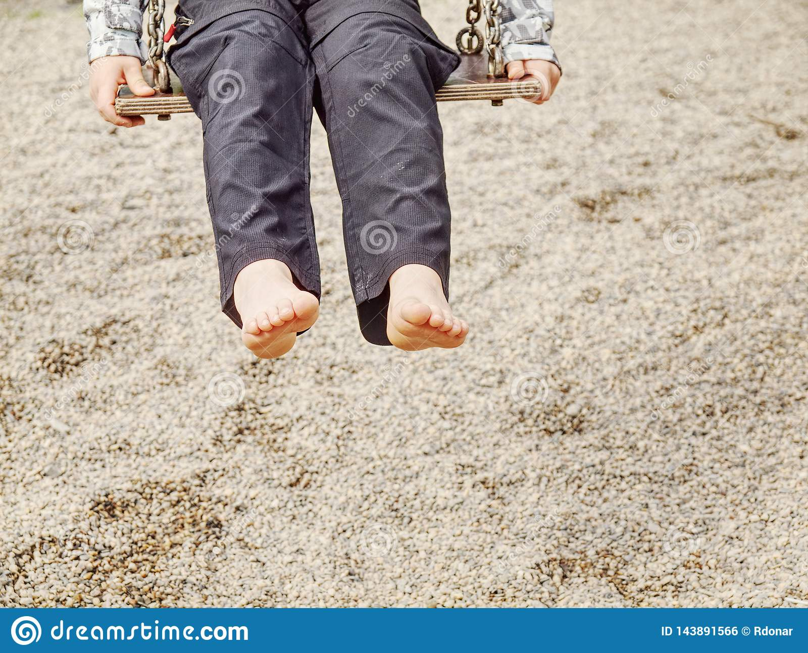 Kid sitting with feet against a sand in summer playground
