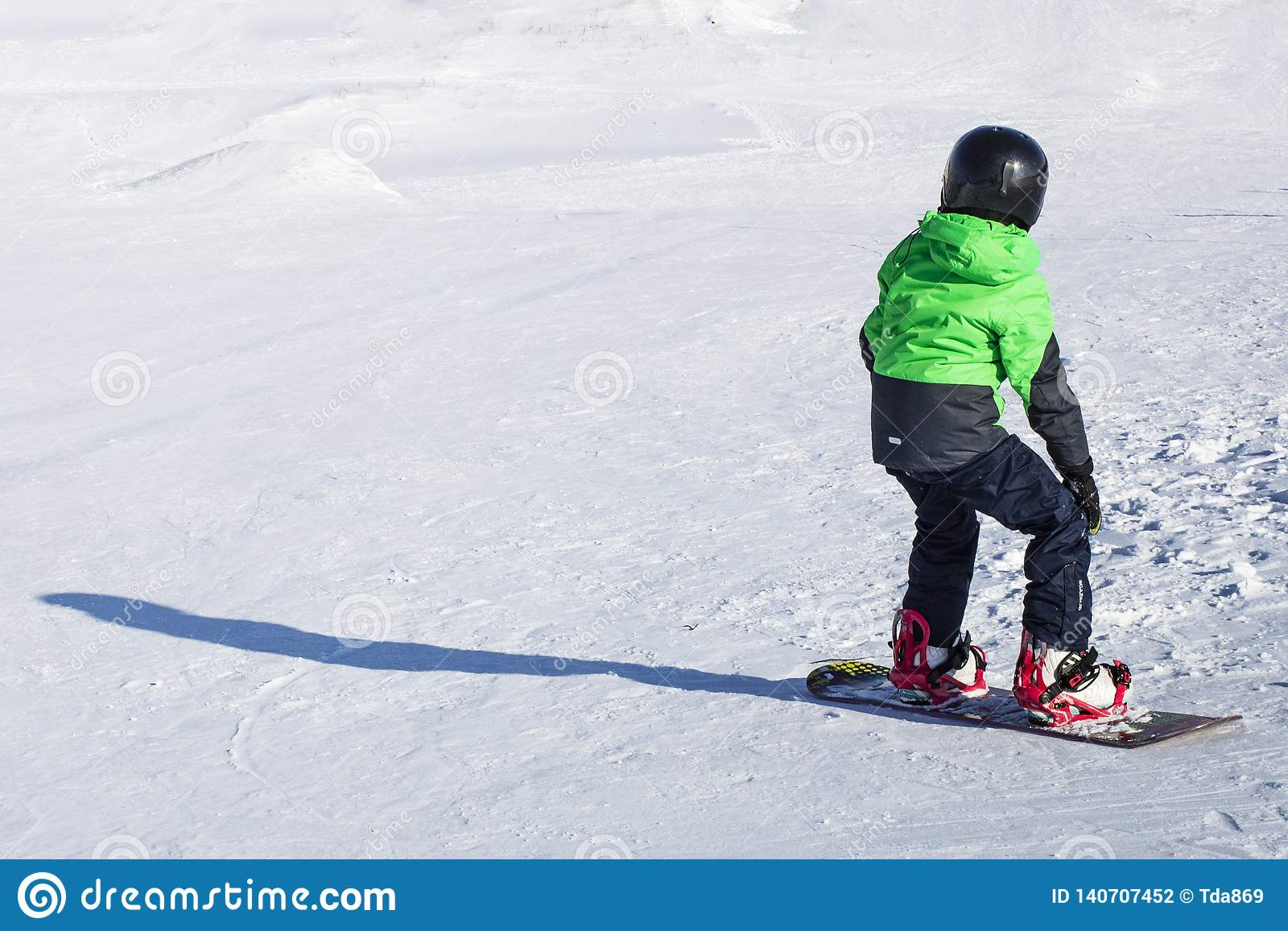 Kid on snowboard in winter sunset nature. Sport photo with edit space
