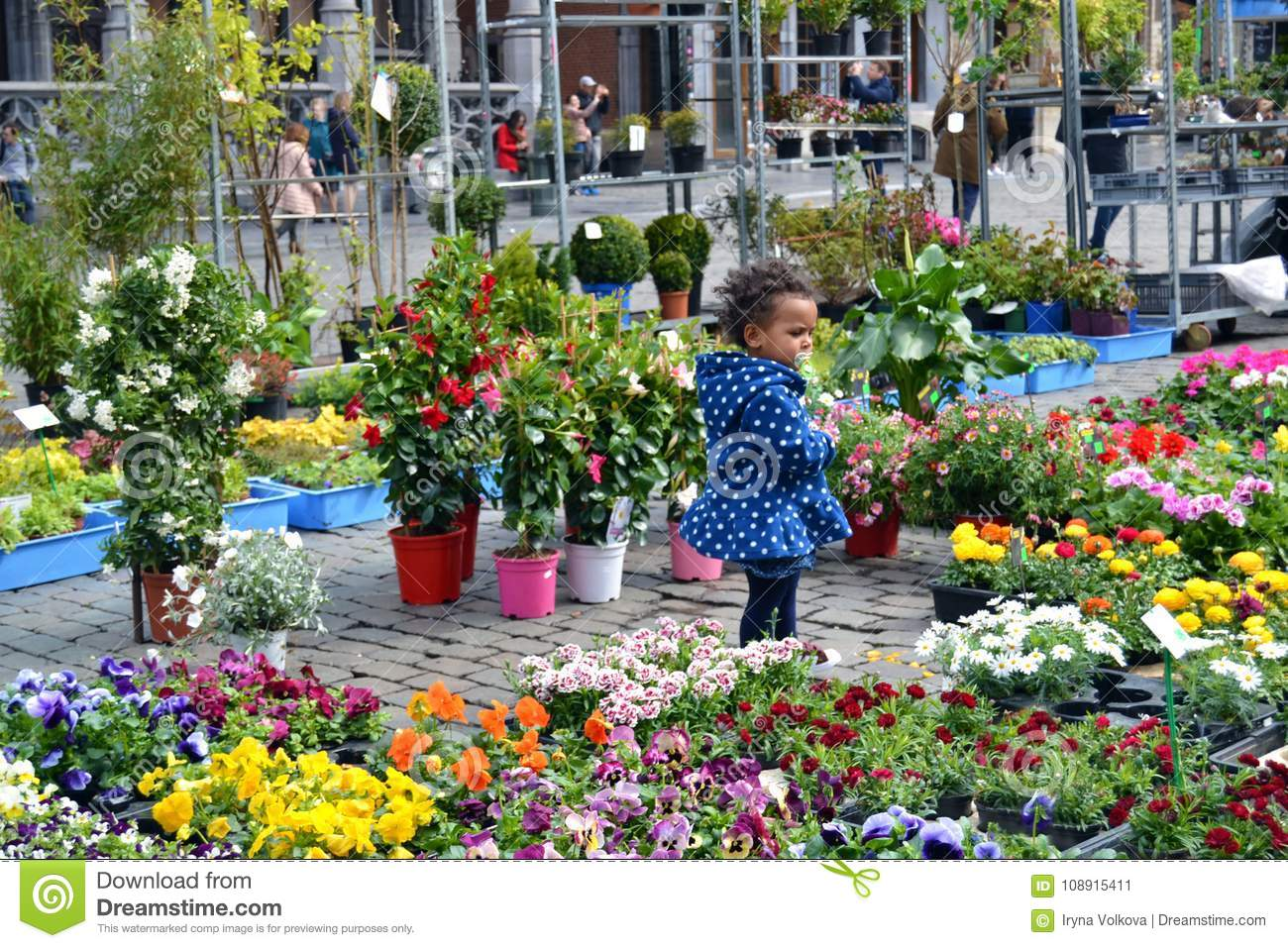 Kid surrounded with flowers on the street